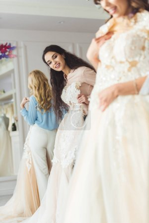 Young smiling bride and bridesmaids choosing dresses in wedding fashion shop