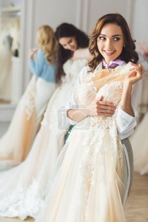 Smiling women with wedding dresses in wedding salon