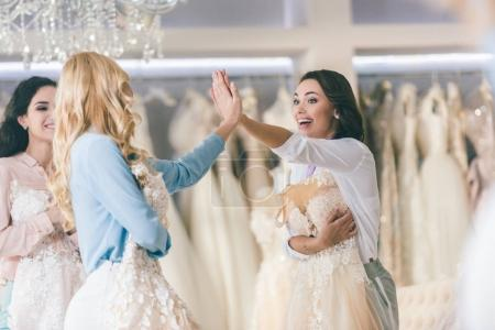 Young smiling brides giving high five in wedding atelier