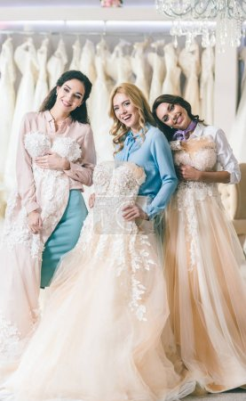 Attractive women with wedding dresses in wedding fashion shop