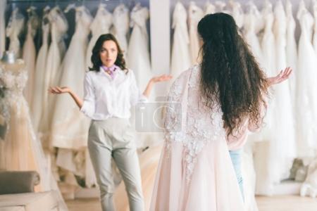 Bride with friend choosing dress in wedding atelier