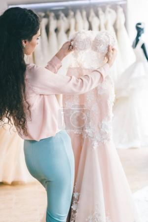 Young female choosing wedding dress in wedding salon