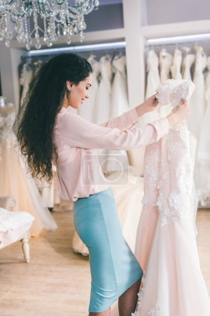 Photo for Brunette bride during dress fitting in wedding salon - Royalty Free Image