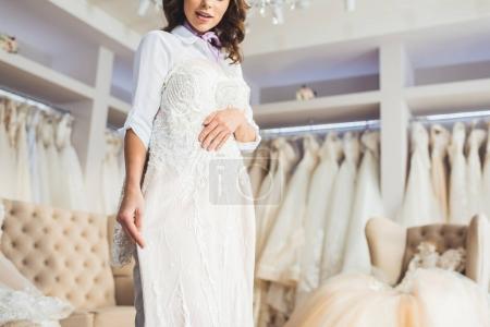 Beautiful bride trying on dress in wedding atelier