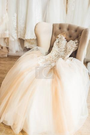 Photo for Lace wedding dress on chair in wedding salon - Royalty Free Image