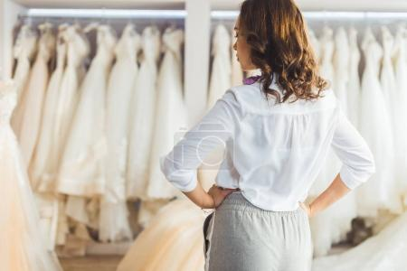 Attractive woman looking at dresses in wedding fashion shop