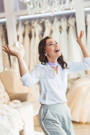 Photo pour Jeune mariée excitée tout en essayant sur la robe dans le salon de mariage - image libre de droit