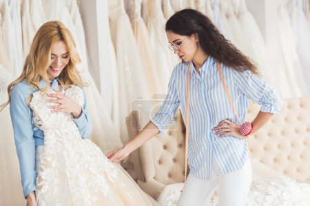Bride holding dress by tailor in wedding salon