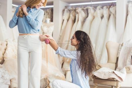 Needlewoman measuring waist of female client in wedding fashion shop