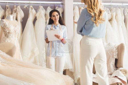 Beautiful bride and female tailor discussing dress design in wedding salon