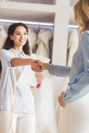 Seamstress and bride shaking hands in wedding atelier