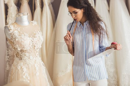 Thoughtful needlewoman with clipboard in wedding salon