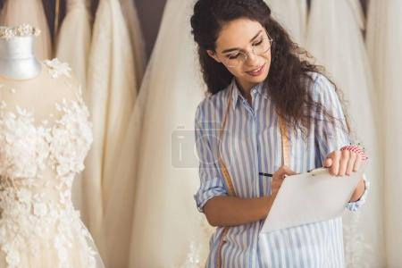 Tailor writing in clipboard by beautiful dress in wedding fashion shop