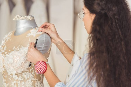 Needlewoman fixing lace dress in wedding fashion shop