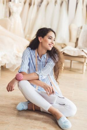 Smiling needlewoman sitting on floor in wedding atelier