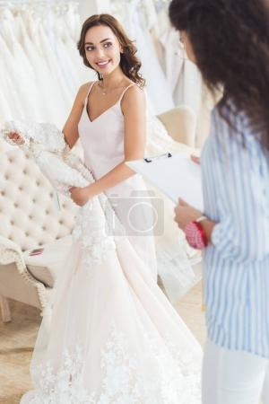 Bride holding dress and tailor writing in clipboard in wedding atelier