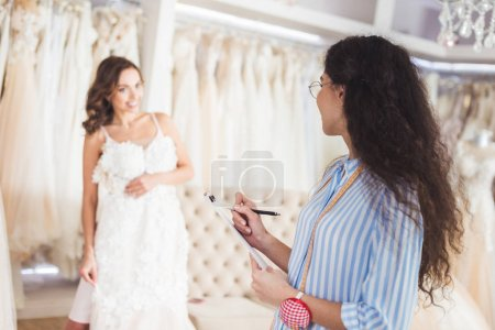 Needlewoman and bride discussing dress design in wedding fashion shop