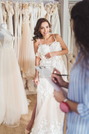 Beautiful bride and female tailor trying on dress in wedding atelier