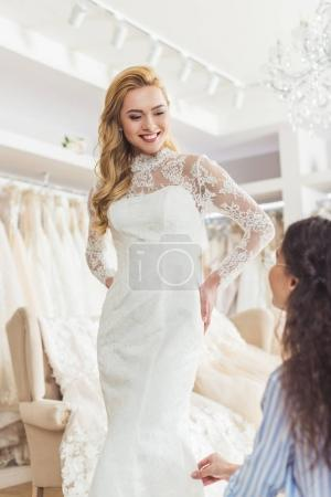 Bride in lace dress and tailor in wedding salon