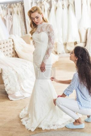 Female tailor working by attractive bride in wedding atelier