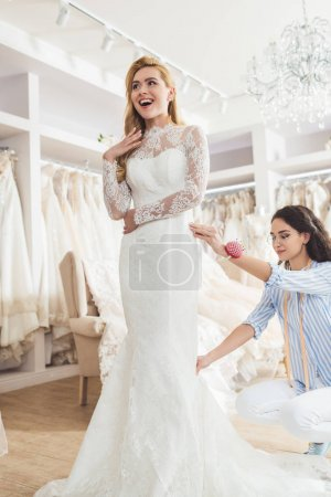 Photo for Blonde bride in lace dress and tailor during dress fitting in wedding salon - Royalty Free Image