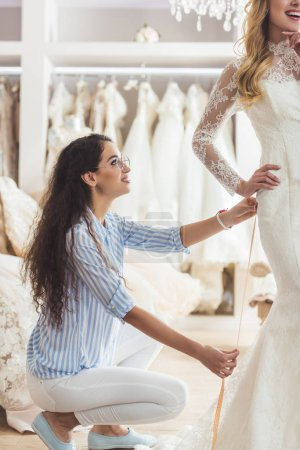 Beautiful bride and female tailor trying on dress in wedding salon