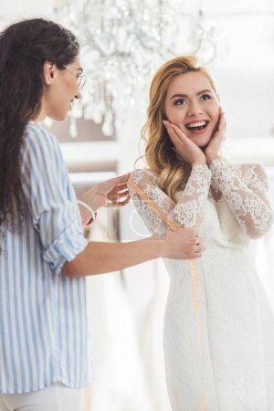 Bride in lace dress and tailor in wedding atelier
