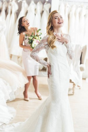 Laughing bride and bridesmaid in wedding fashion shop