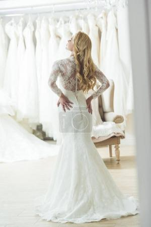 Young bride in lace dress in wedding atelier