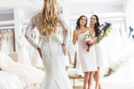 Young bride and bridesmaids with bouquets in wedding fashion shop
