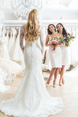 Bridesmaids with flowers looking at beautiful bride in wedding atelier
