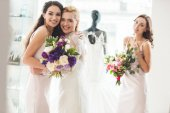 Bride in lace dress and bridesmaids with flowers in wedding salon