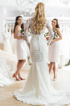 Attractive bride and bridesmaids with flowers in wedding atelier