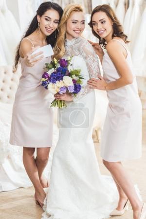 Attractive women in wedding dresses taking selfie in wedding salon