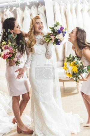 Young smiling bride and bridesmaids with bouquets in wedding fashion shop