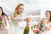 Young smiling bride and bridesmaids opening champagne in wedding fashion shop