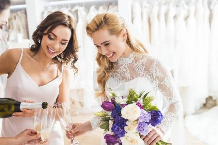 Young brides holding champagne glasses and bottle in wedding fashion shop