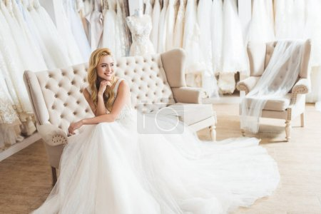 Photo for Young bride in tulle dress sitting on sofa in wedding salon - Royalty Free Image