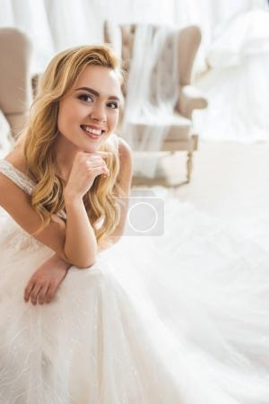 Smiling bride wearing tulle dress in wedding atelier
