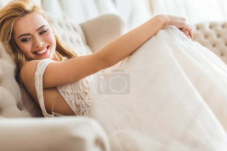 Young blonde bride wearing tulle dress in wedding salon
