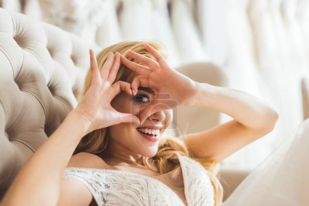 Blonde bride showing heart sign in wedding fashion shop