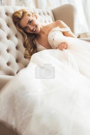 Smiling bride wearing tulle dress sitting on sofa in wedding atelier