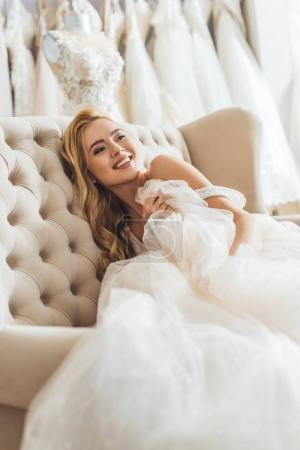 Attractive bride resting on sofa in wedding salon