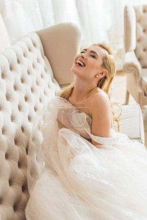 Beautiful bride in tulle dress on sofa in wedding atelier