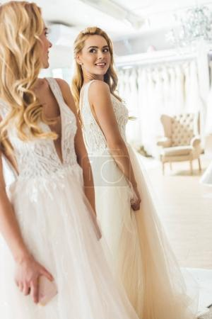 Young bride in white dress by mirror in wedding fashion shop