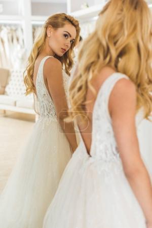 Attractive woman wearing wedding dress by mirror in wedding atelier