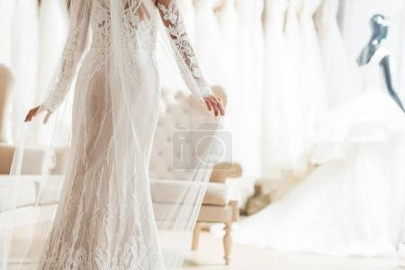 Cropped view of bride in lace dress in wedding salon