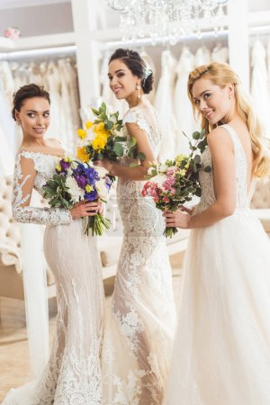 Attractive brides holding bouquets in wedding atelier