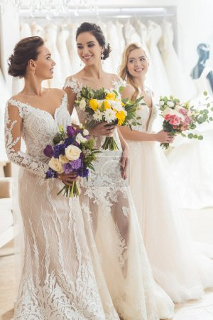 Smiling women in wedding dresses with flowers in wedding atelier