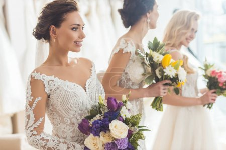 Young smiling brides with bouquets in wedding fashion shop